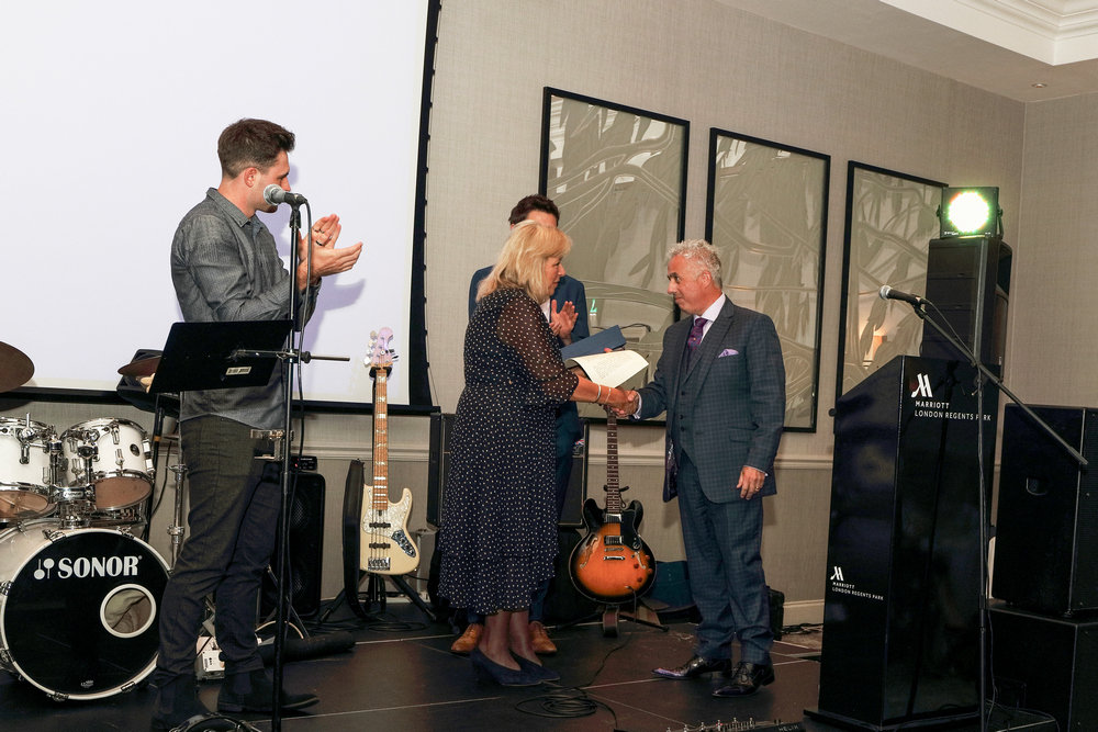 Picture of Donna  presented with a glass plaque by Mark